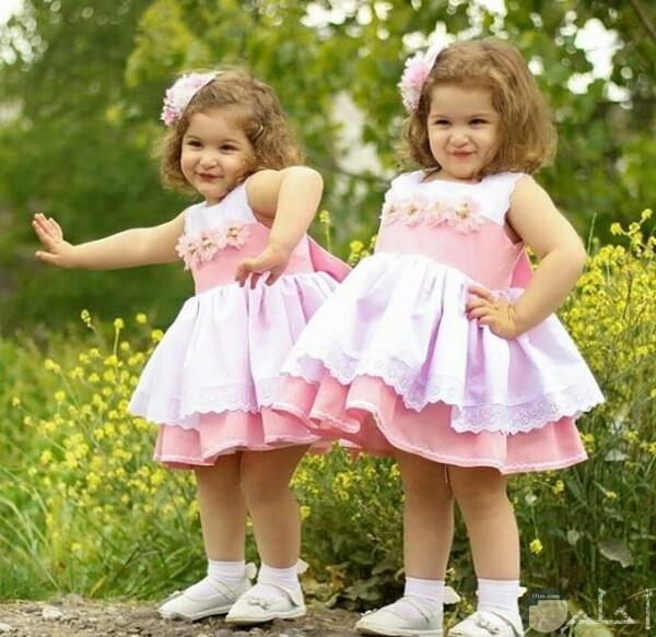 صورة جميلة جدا لبنتين صغيرتين واقفتين في الحديقة ترتديان فستان وردي