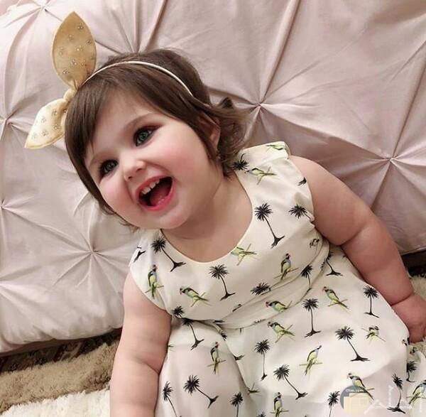 صورة جميلة جدا لبنت صغيرة جالسة بفستان أبيض حلو مرسوم عليه طيور ونخل