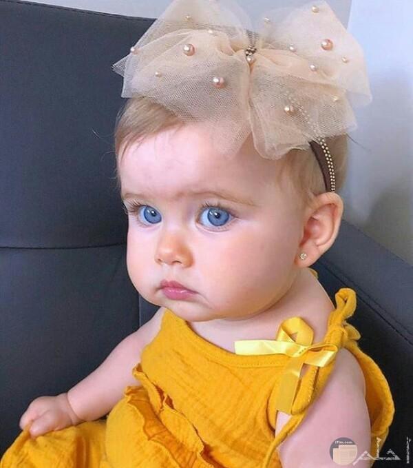 صورة جميلة جدا لبنت صغيرة جالسة بفستان أصفر حلو