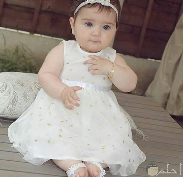 صورة جميلة جدا لبنت صغيرة جالسة ترتدي فستان أبيض حلو