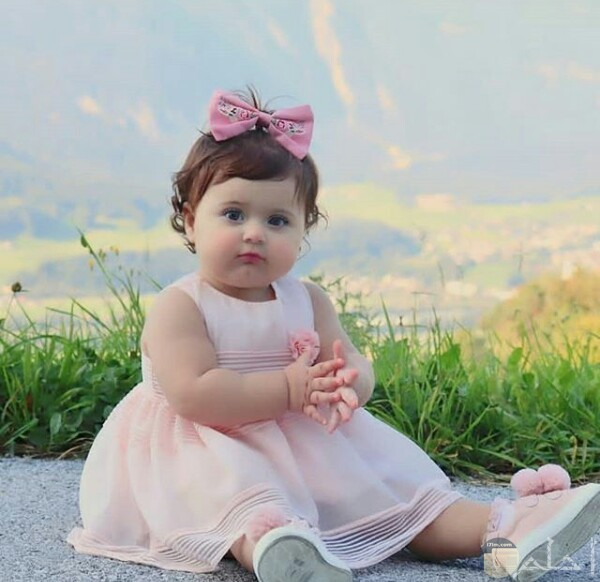 صورة جميلة جدا لبنت صغيرة جالسة علي الأرض ترتدي فستان وردي حلو