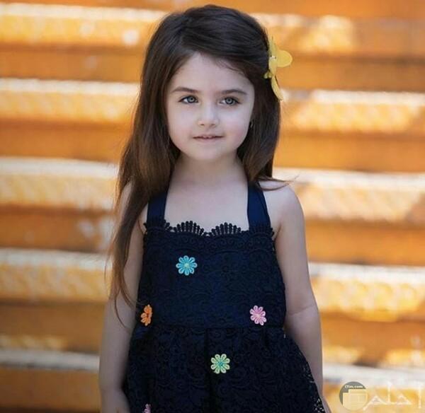 صورة جميلة جدا لبنت صغيرة مرتديه فستان أزرق حلو مع خلفية مميزة