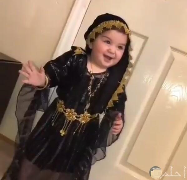 صورة جميلة جدا لبنت صغيرة واقفة مرتديه فستان أسود مزين حلو
