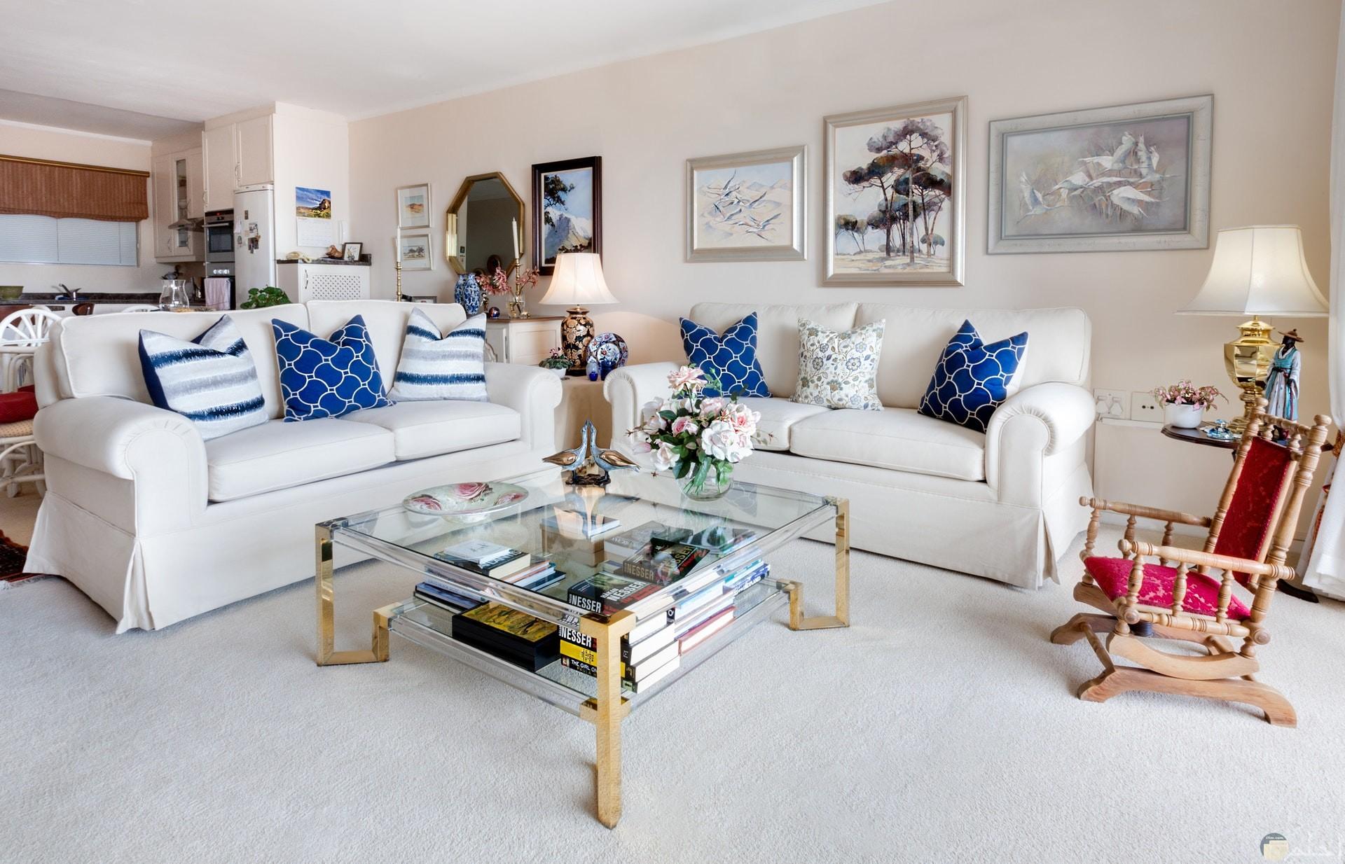 صورة جميلة لديكور أنيق حيث تناسق الكنب باللون الأبيض مع اللوحات والمنضدة الزجاجية وألوان الحوائط