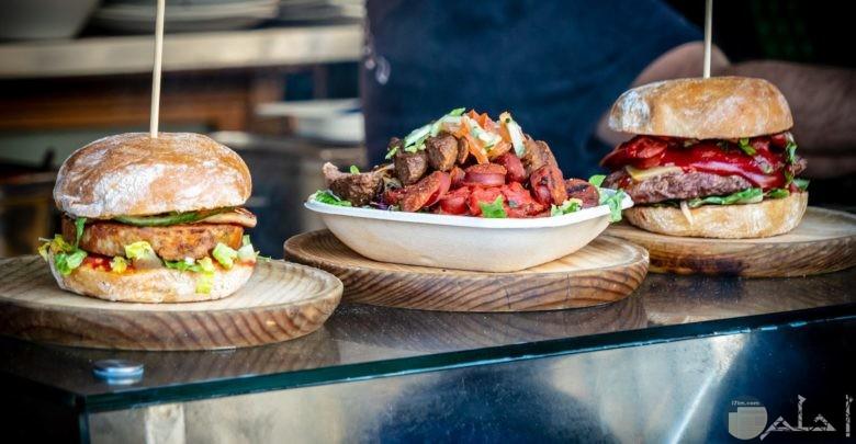 صورة جميلة لساندوتشين برجر لذيذين مع طبق من اللحم في الوسط