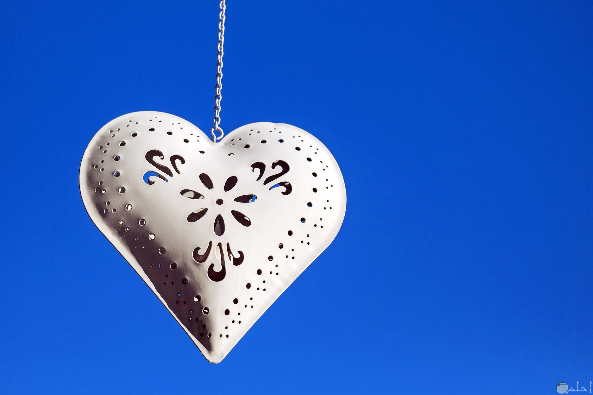 صورة جميلة لسلسلة علي شكل قلب أبيض مع خلفية زرقاء