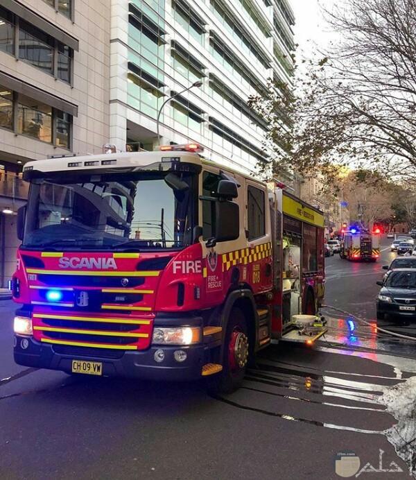 صورة جميلة لسيارة الإطفاء في أحد الشوارع وخلفها سيارات أخري عادية