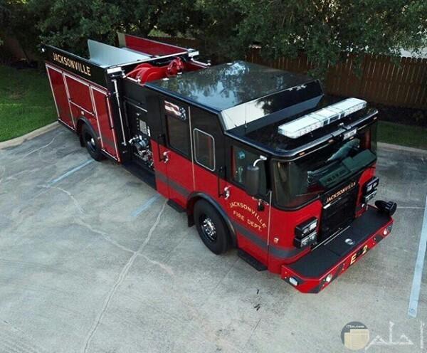 صورة جميلة لسيارة الإطفاء مركونة وخلفها حديقة وشجر