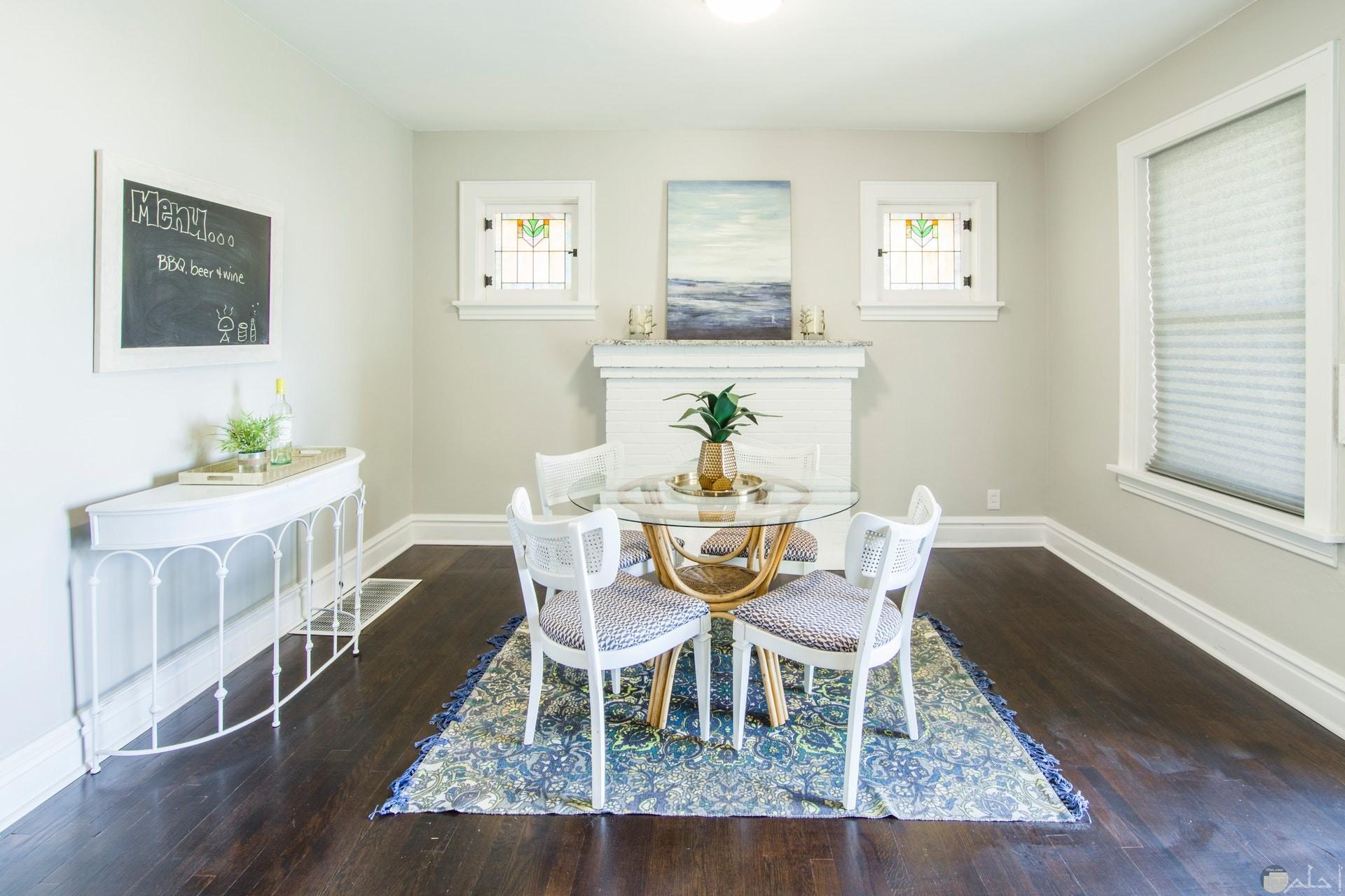 صورة جميلة لغرفة بها كراسي وطاولة صغيرة زجاجية مع لوحة جميلة وعدم وجود إزدحام بالغرفة