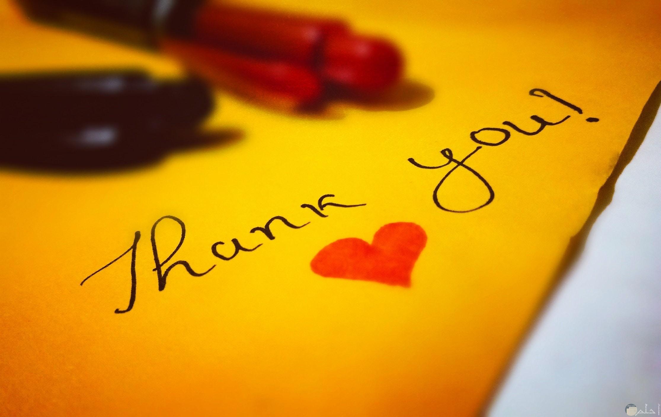 صورة جميلة للتعبير عن الشكر بالإنجليزي مكتوبة علي ورقة صفراء معاها قلب أحمر وقلمين