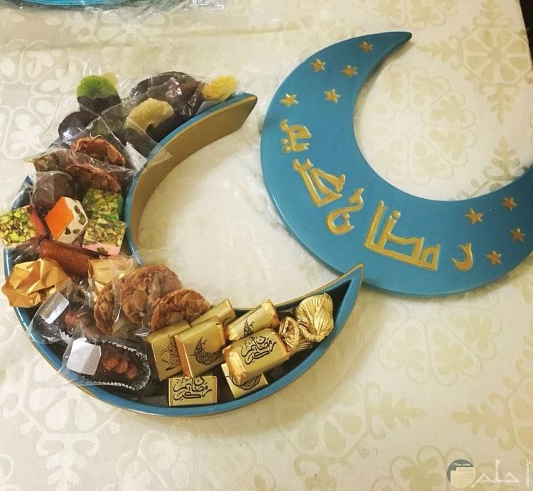 صورة جميلة للتهنئة بشهر رمضان فيها علبة حلويات لذيذة مكتوب علي غطائها رمضان كريم