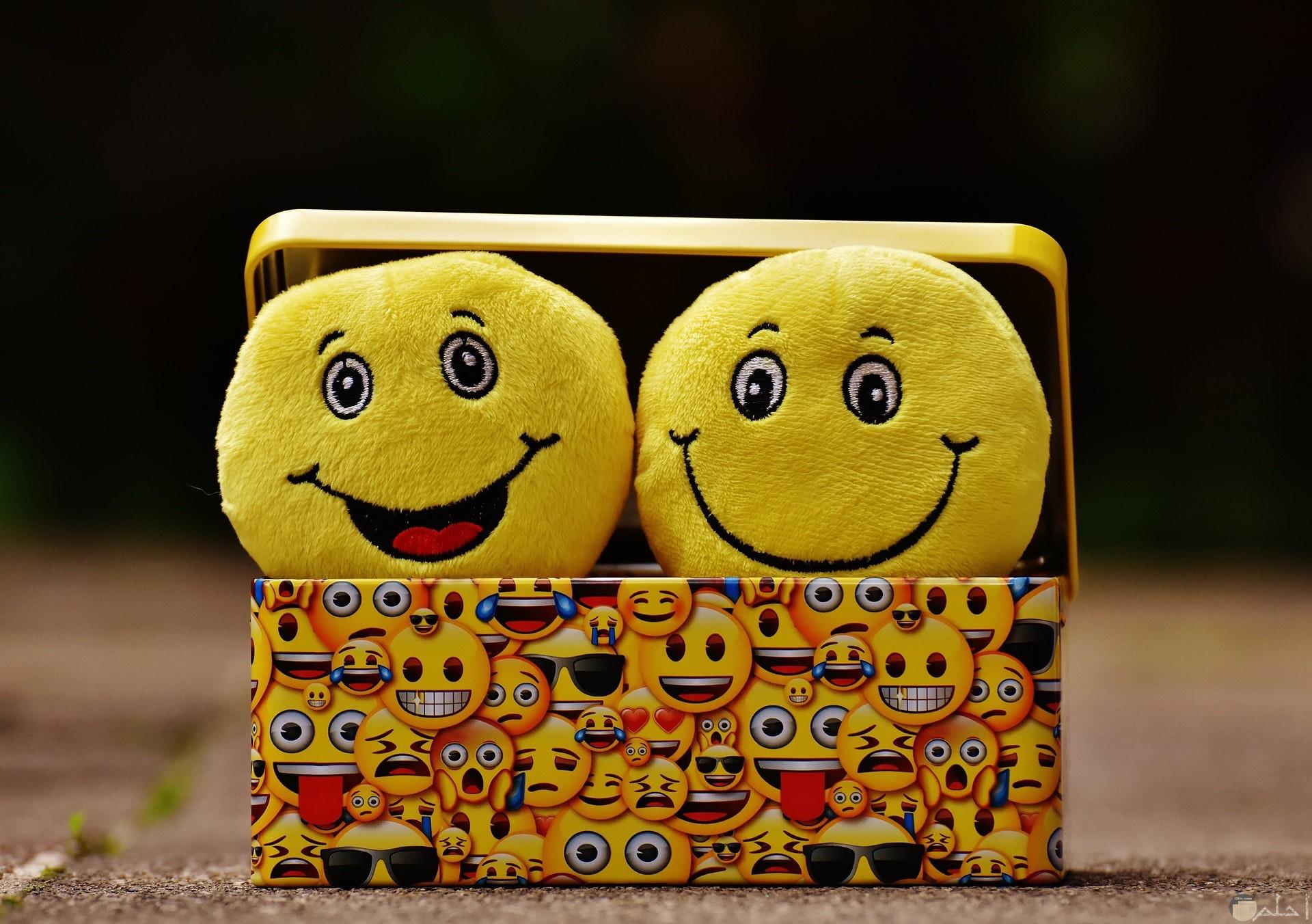 صورة جميلة لمجموعة الإيموجي المختلفة مجتمعة معا علي الصندوق وداخل الصندوق إتنين إيموجي مبتسم وضاحك