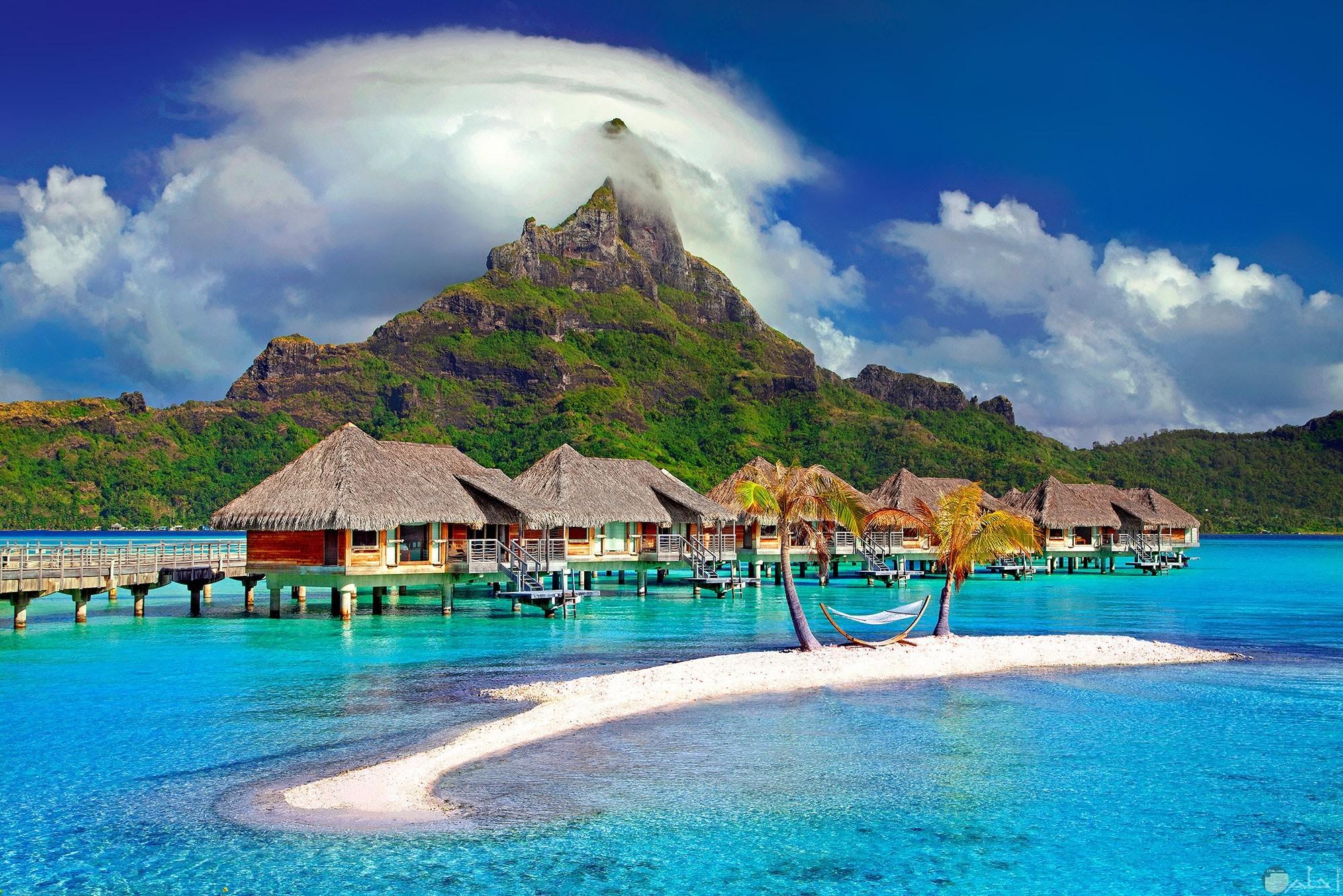 صورة جميلة لمجموعة من الأكواخ مع بحر صافي جميل وجبل عليه مسطحات خضراء