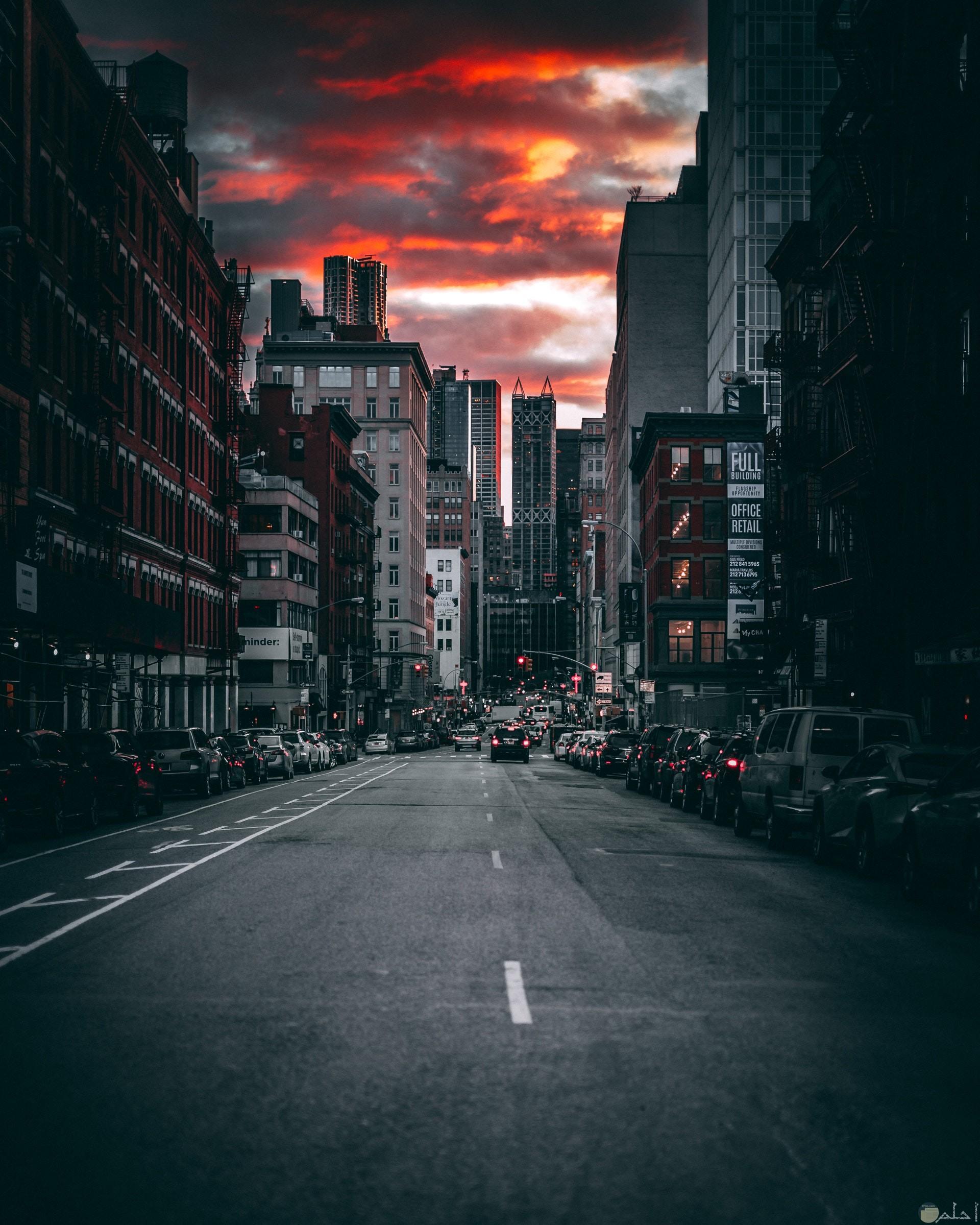 صورة جميلة ومميزة لشارع به مباني وسيارات وقت الغروب