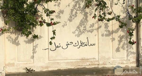 صورة حزينة جدا مكتوب عليها كلام عن الشوق والإنتظار علي الحائط