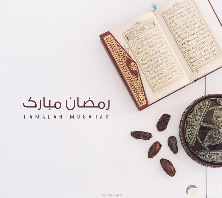 صورة حلوة للتهنئة بشهر رمضان بجملة رمضان مبارك بجانبها مصحف وخمس تمرات