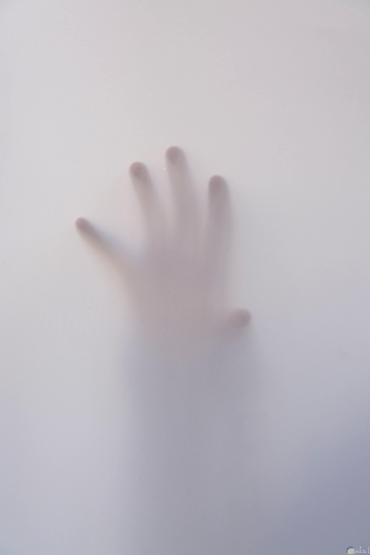 صورة رعب لشخص بمكان مخيف يحاول الهرب لكن تظهر يده فقط من وراء حاجز