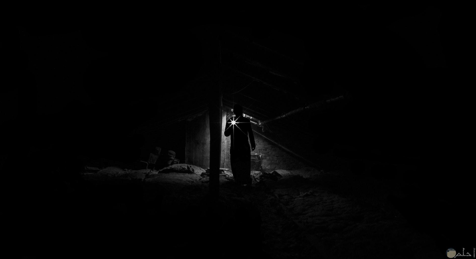صورة رعب لشخص في مكان مخيف ومظلم ممسك بكشاف للإضاءة فقط