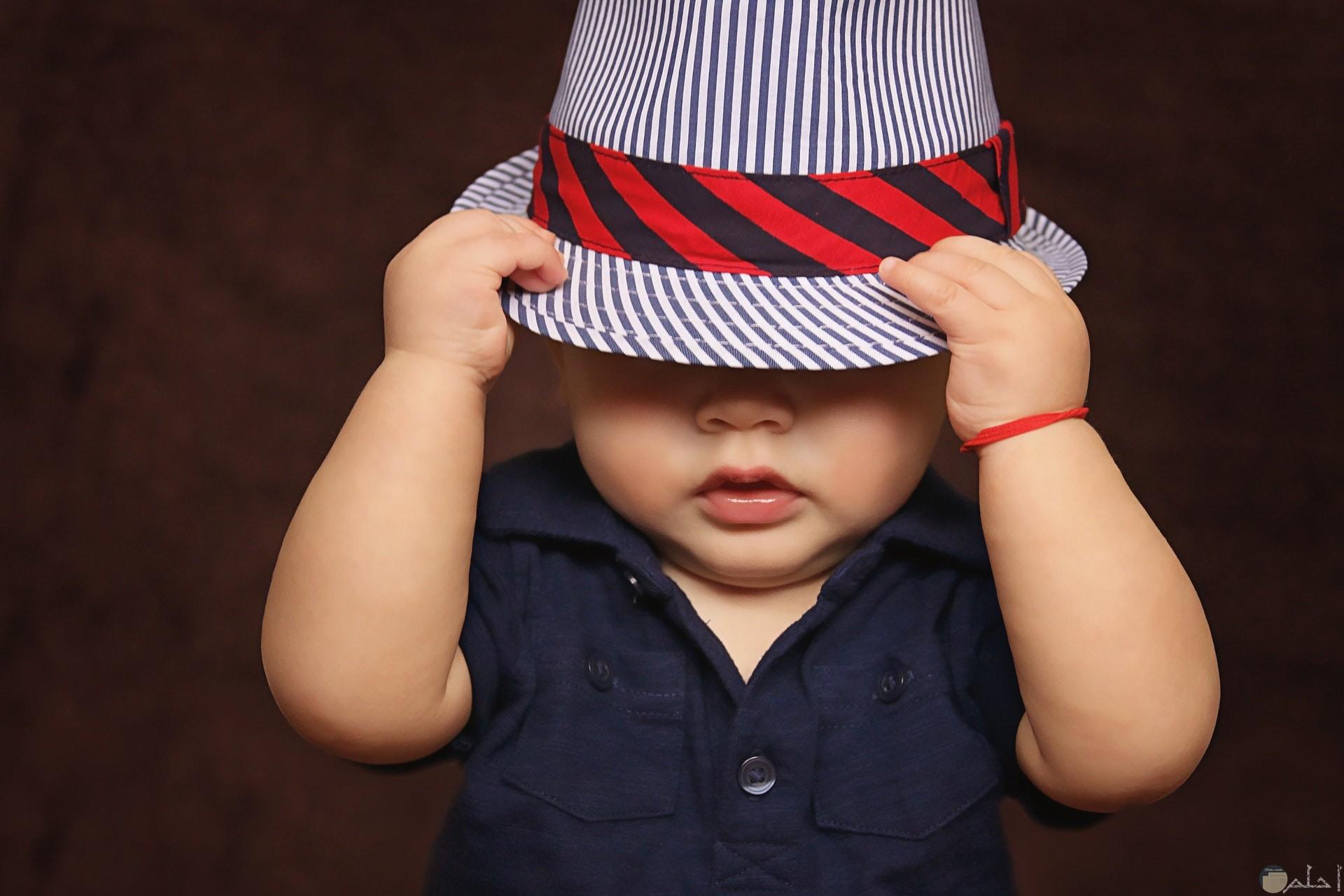 صورة رومانسية لطفل صغير يرتدي قبعة علي رأسه من الخجل