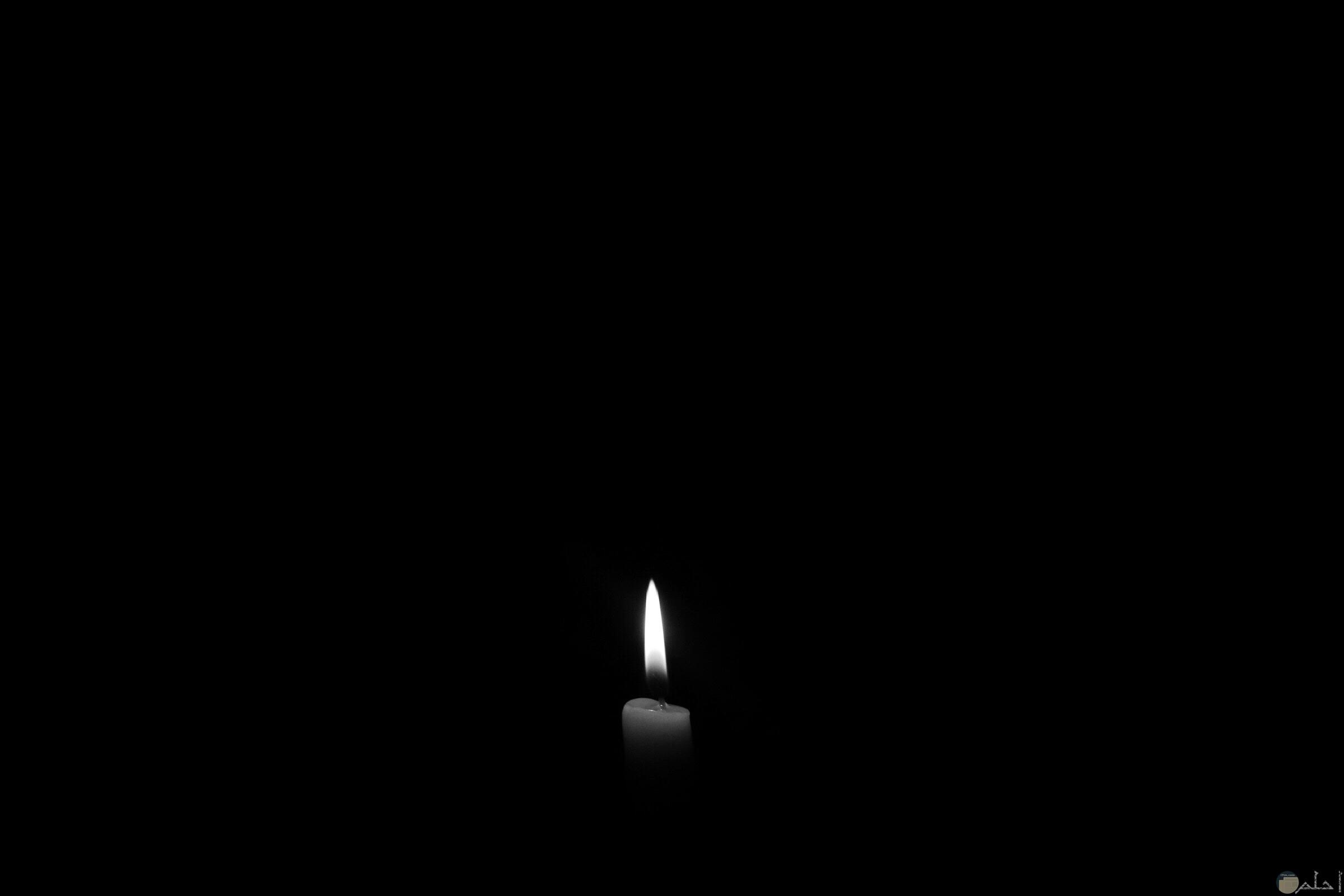 صورة سادة سوداء غامقة بها ضوء شمعة