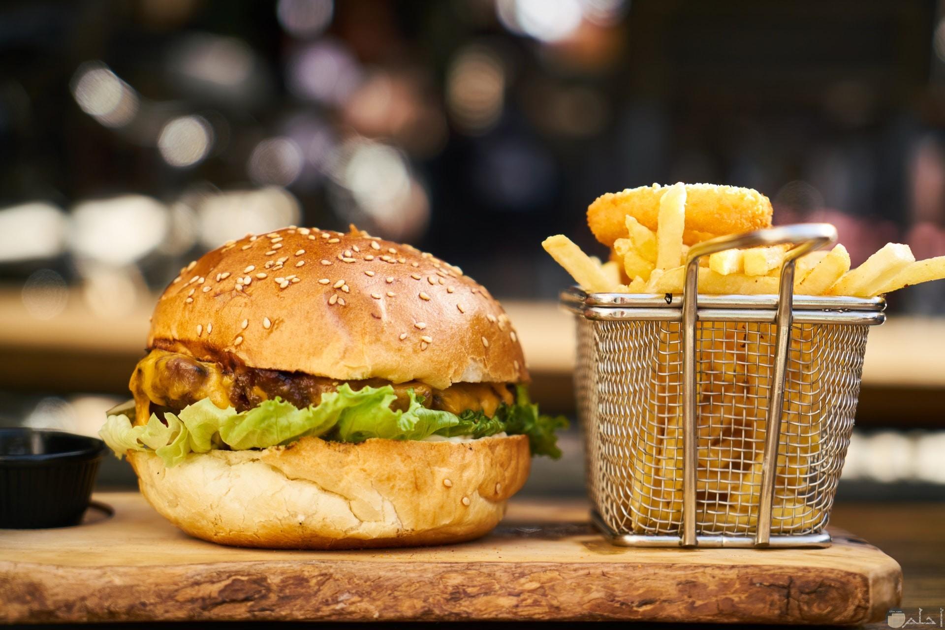 صورة ساندوتش برجر لذيذ مع بطاطس شهية بجانبه