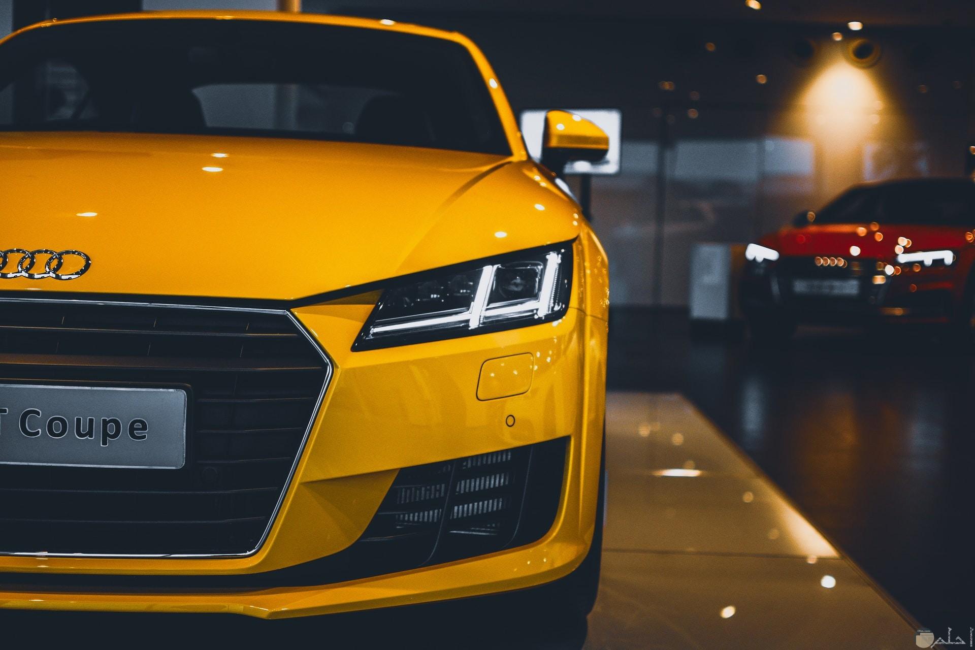 صورة سيارة أودي صفراء فخمة جميلة ومميزة جدا خلفها سيارة حمراء