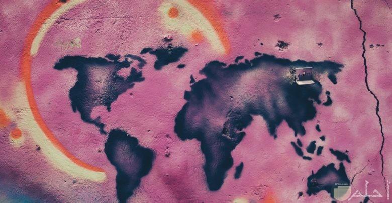 صورة غريبة وجميلة لخريطة الكرة الأرضية مرسومة علي حائط بخلفية ورديه