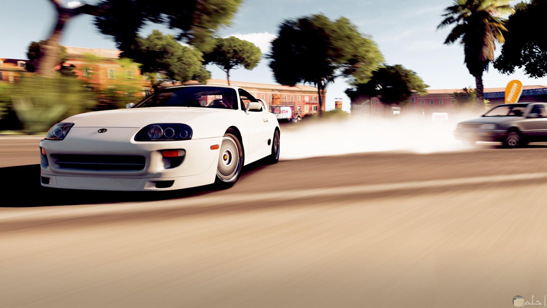 صورة فخمة لسيارة كوبيه بيضاء تجري في الطريق وخلفها سيارة أخري