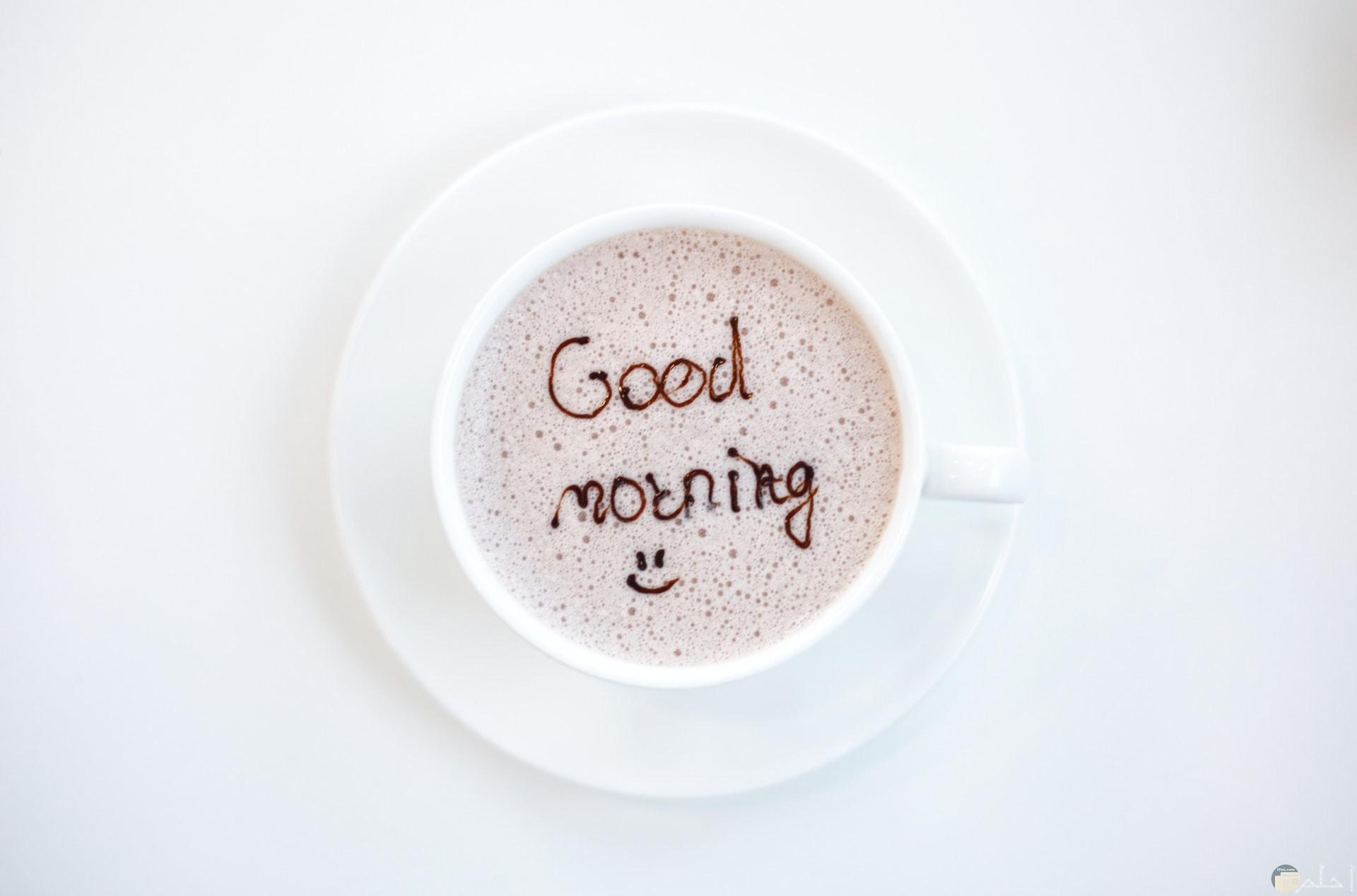 صورة لتحية الصباح بالإنكليزية مكتوبة داخل فنجان القهوة معها ايموشن مبتسم