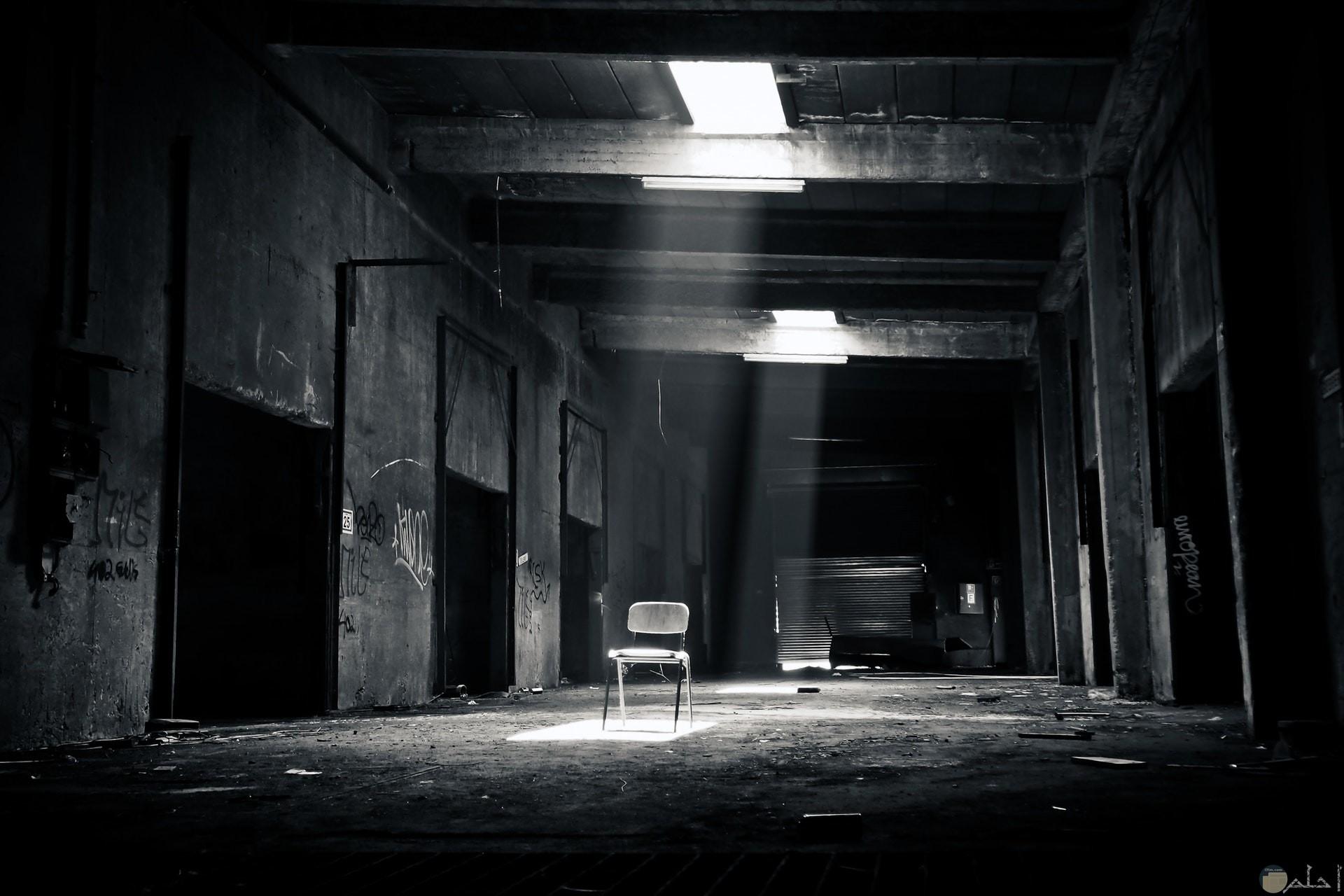صورة مخيفة بالأبيض والاسود لمكان مهجور ويوجد كرسي يصل له النور