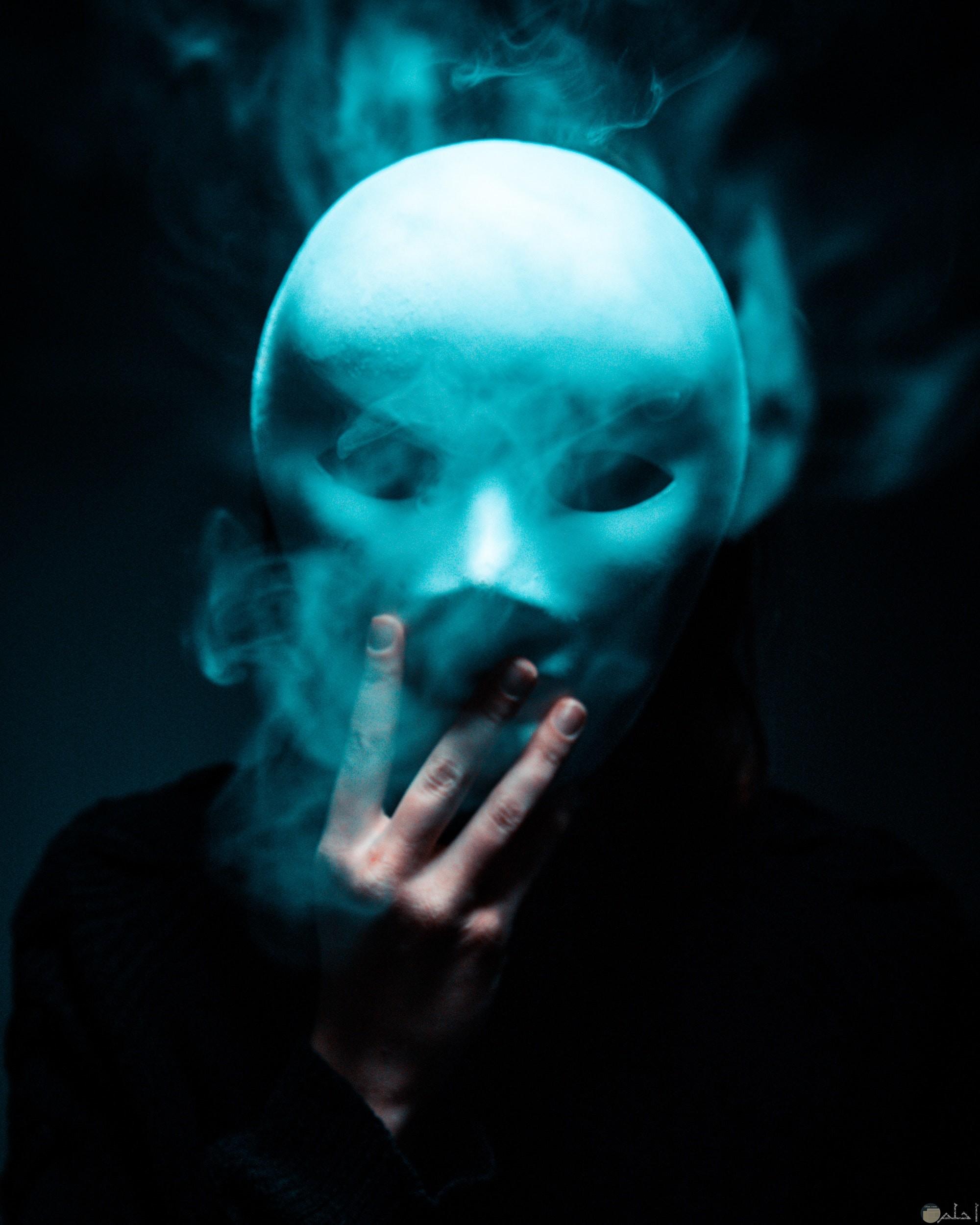 صورة مرعبة لشخص يرتدي قناع مخيف ويخلعه
