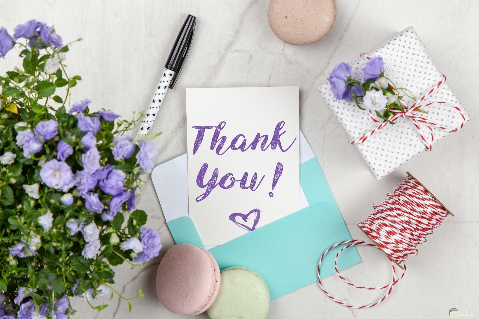 صورة مميزة جدا لشكرا للأصدقاء مكتوبة باللون البنفسجي وبجانبها باقة ورد بنفسجية وقلم وهدية مغلفة