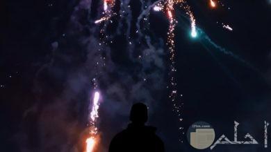 صورة مميزة جدا للألعاب النارية في السماء وشاب يراقب جمال ألوانها