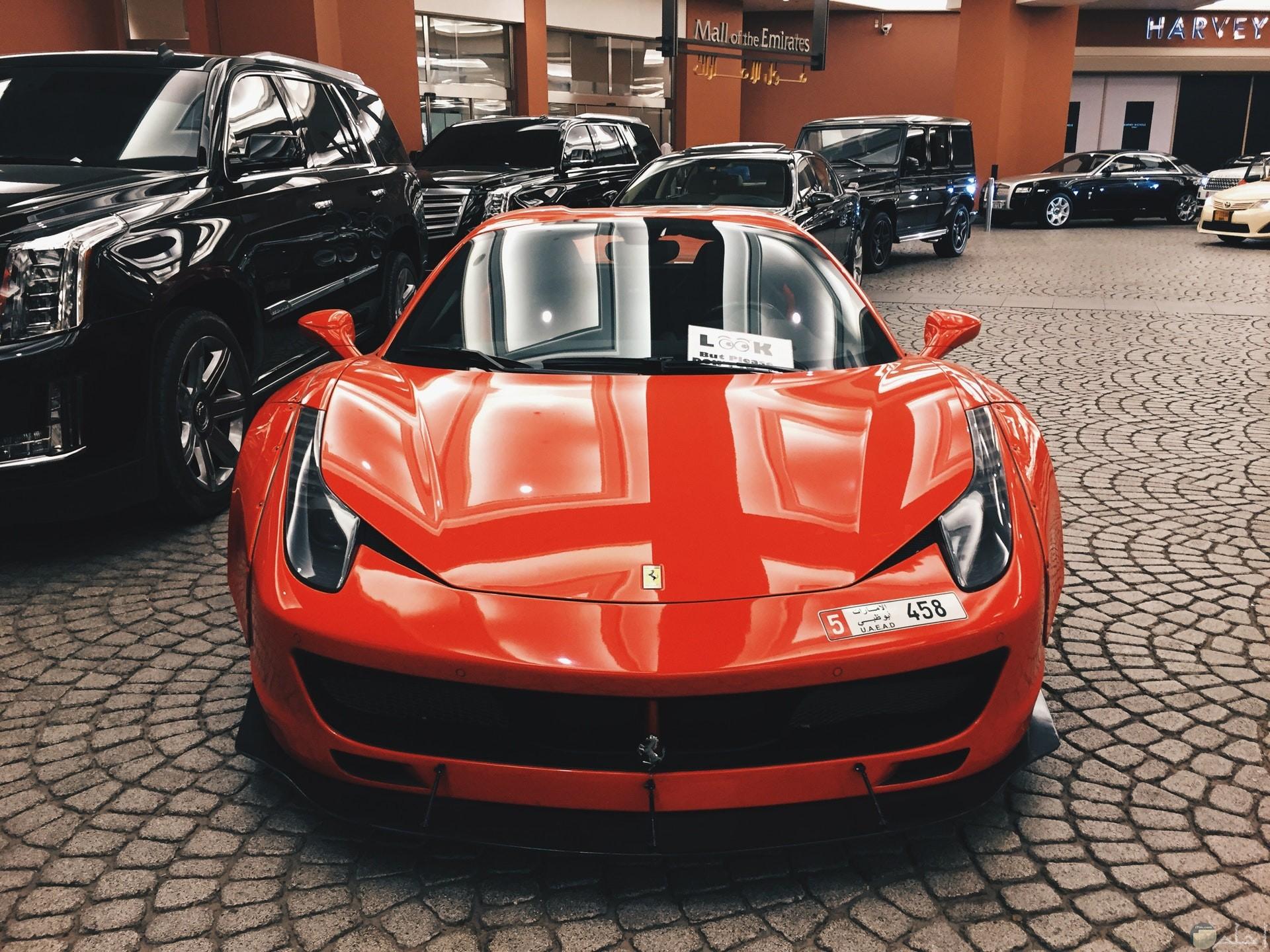 صورة مميزة لسيارة فيراري برتقالية فخمة جدا وخلفها سيارات سوداء