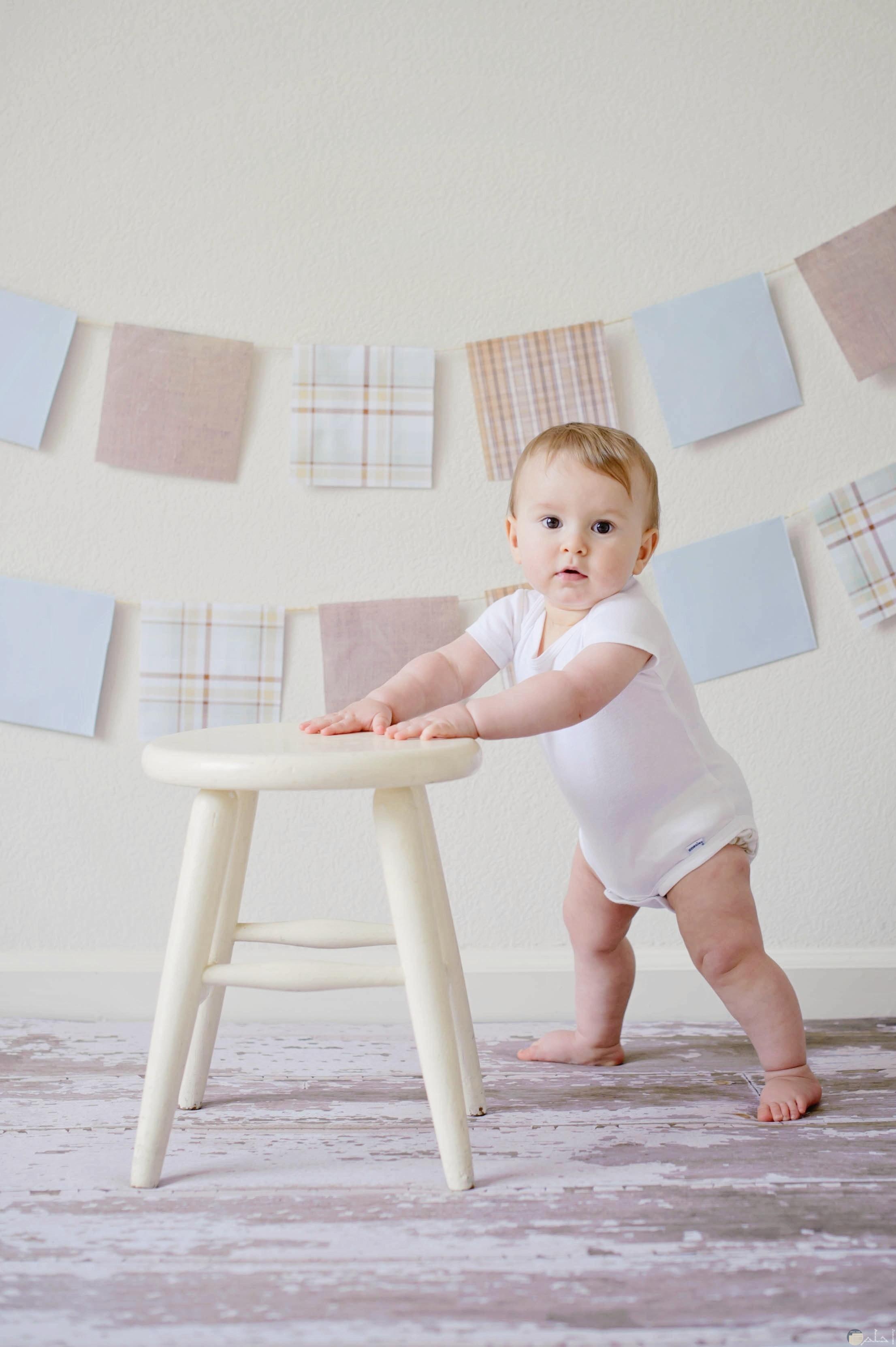 صورة مميزة لطفل صغير جميل يسند علي الكرسي