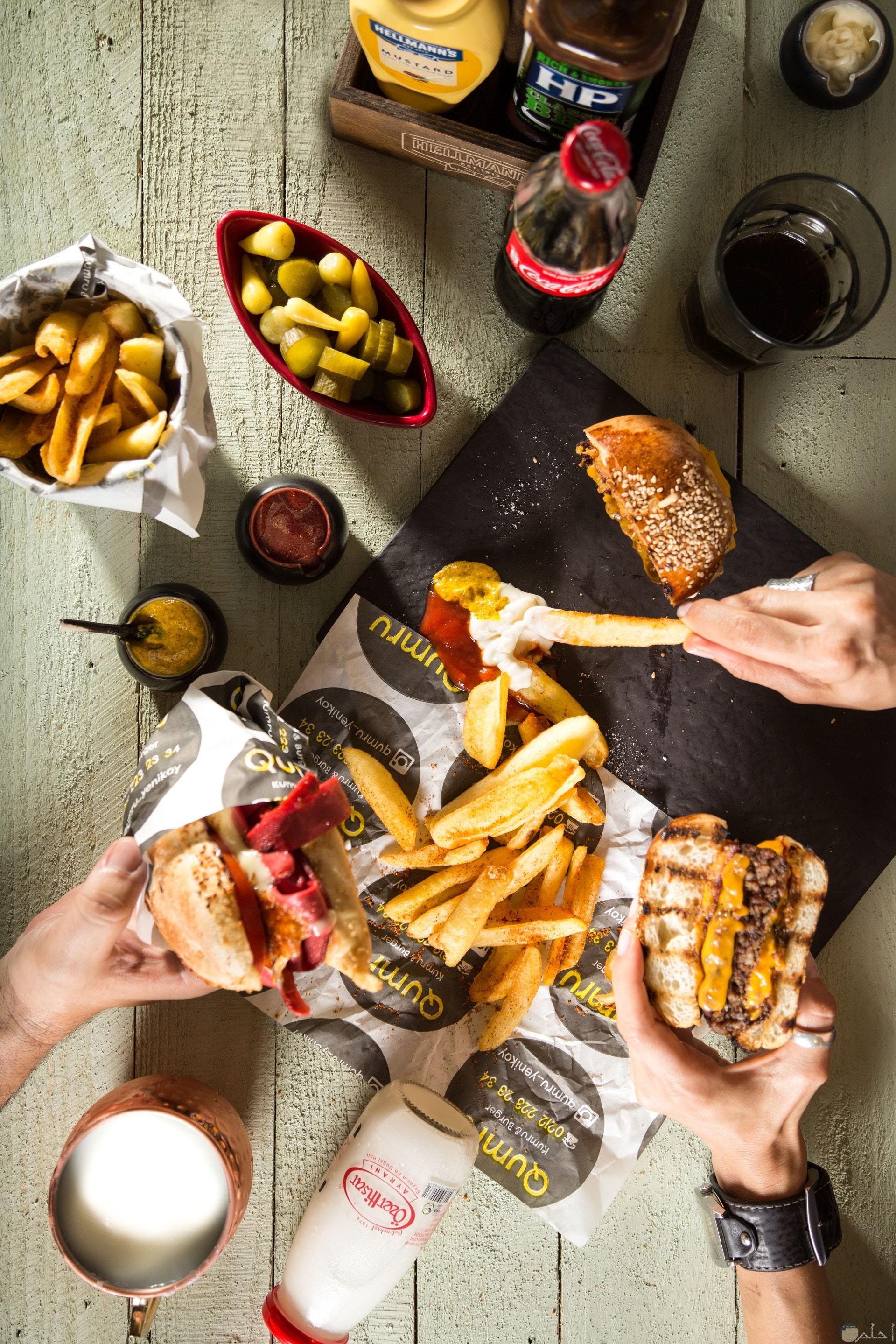 صورة مميزة لمجموعة من الأصدقاء يأكلون البرجر مع البطاطس