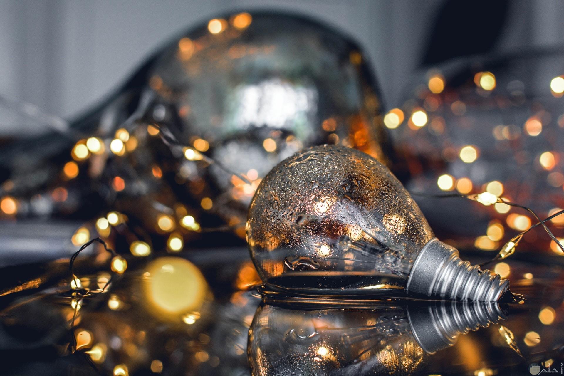صورة مميزة لمصباح في الماء مع مجموعة أنوار حوله تصلح كخلفية جميلة لهاتفك