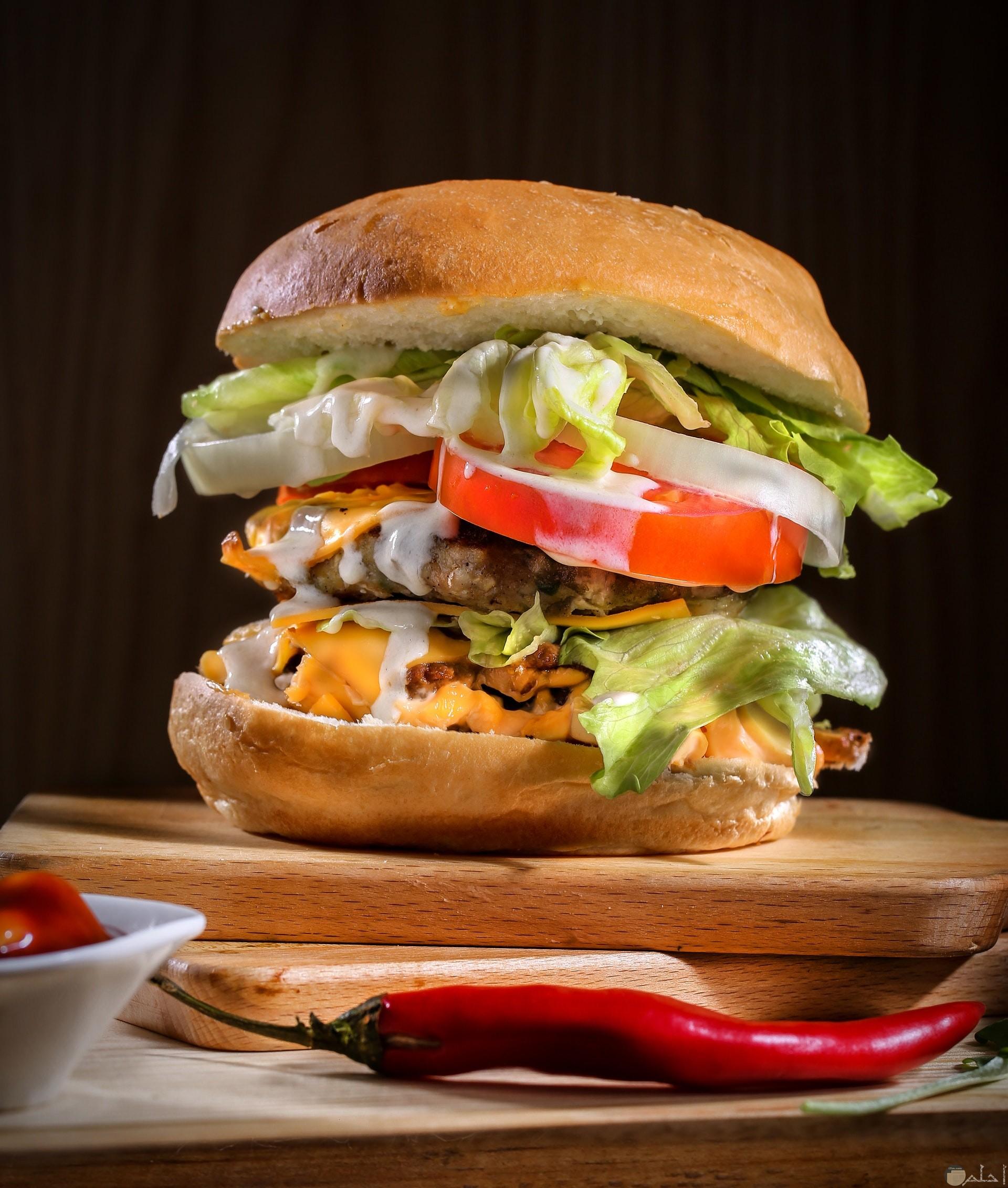 صورة وجبة ساندوتش برجر شهي مع قرن أحمر حار