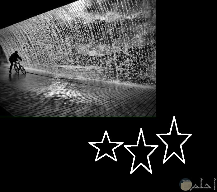 رجل يركب الدراجه بجوار منظر طبيعي لشلال ماء من الداخل