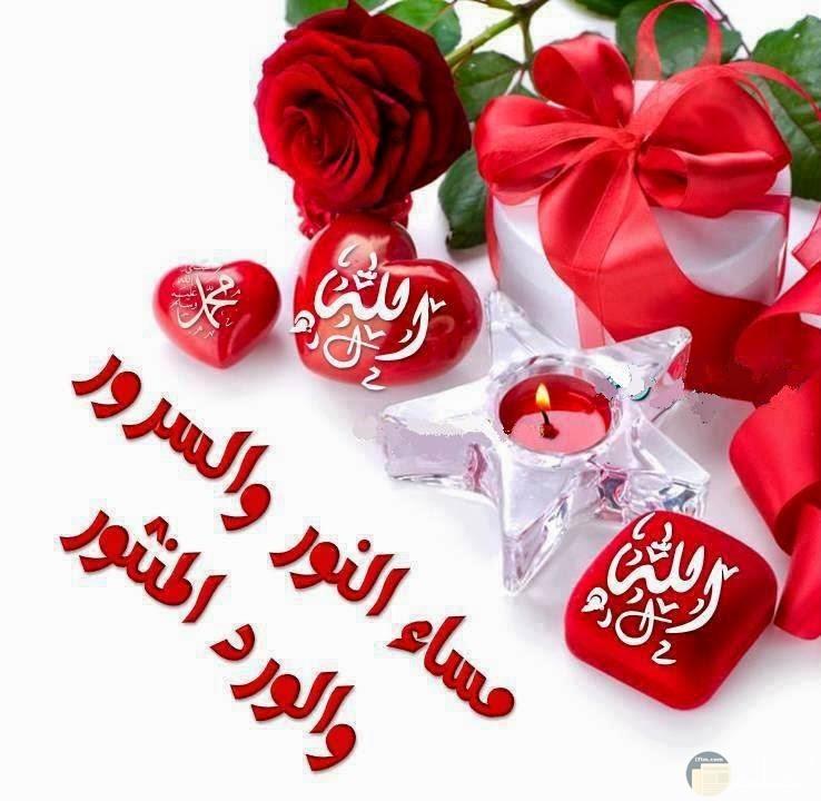 هديه بفيونكه حمراء وعلبه بيضاء وورود من حولها واسم الله علي قلب ومربع احمر وتحيه مساء النور والسرور