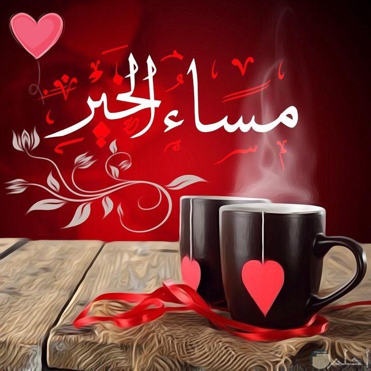 مساء الخير تحيه مع اتنين مج اسمر مرسوم عليهم قلب احمر زبجوارهم شريطه حمراء