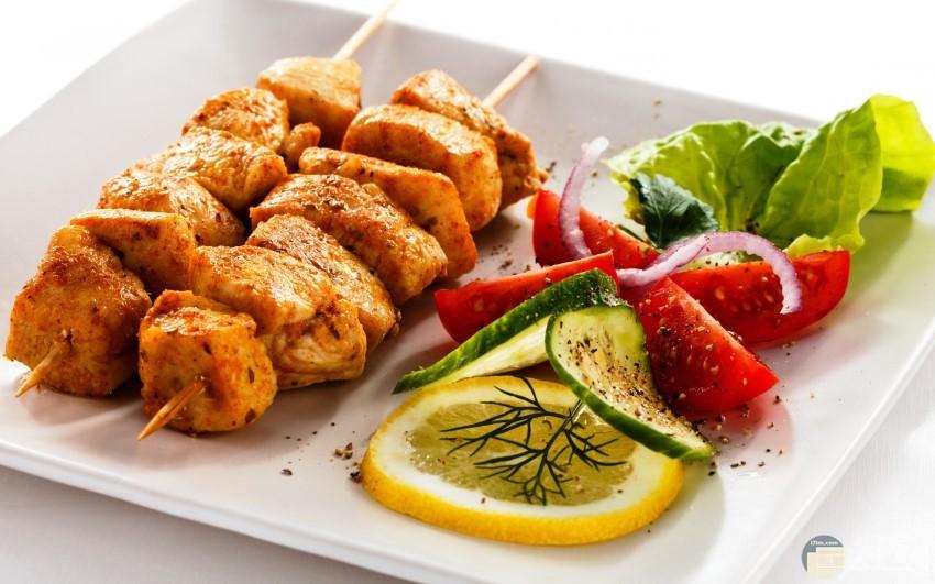 شرائح لحم علي الفحم وطماطم وشرائح ليمون وخيار وبصل