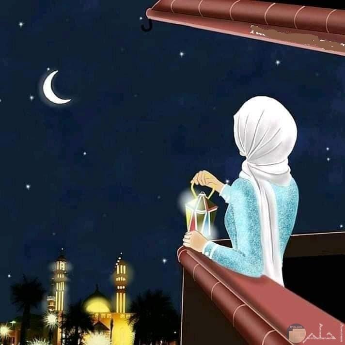 فتاه محجبه بيدها فانوس تنظر الي القمر