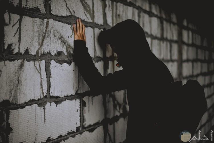 شخص يضع يده علي الحائط ويرتدي ملابس سوداء