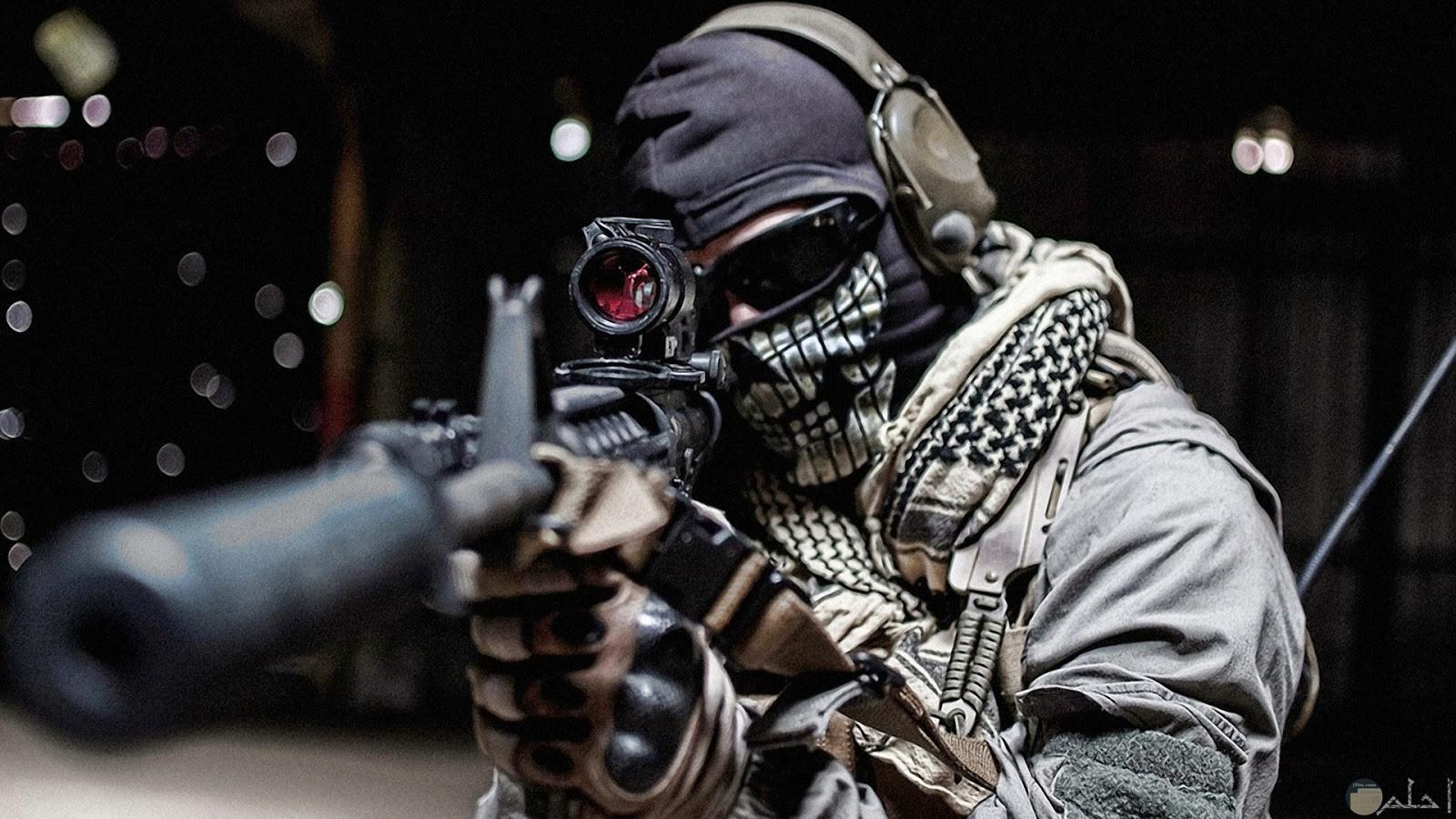 رجل ملتم وبيده سلاح ويرتدي نظاره