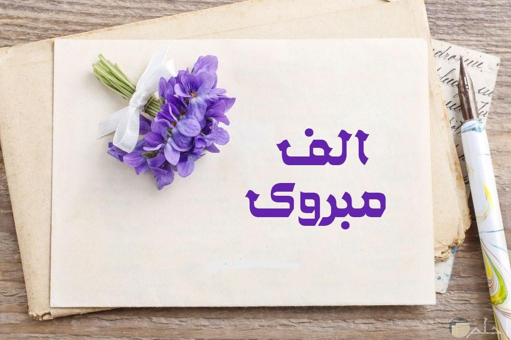 برقيه عليها ورده بنفسج في ابيض مكتوب علي البرقيه الف مبروك للتحيه وبجوارها قلم