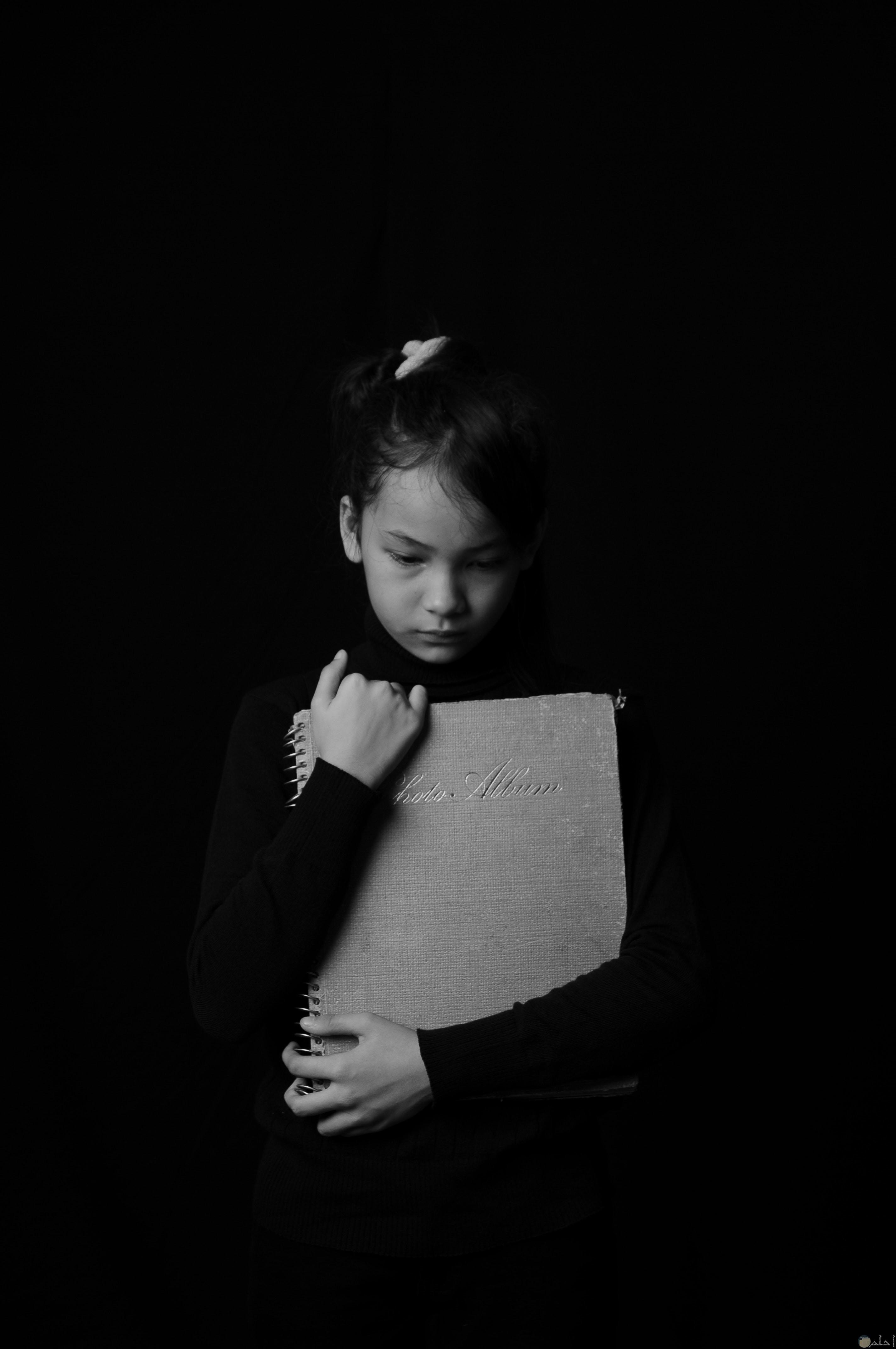 صورة طفلة حزينة تمسك بالكتب