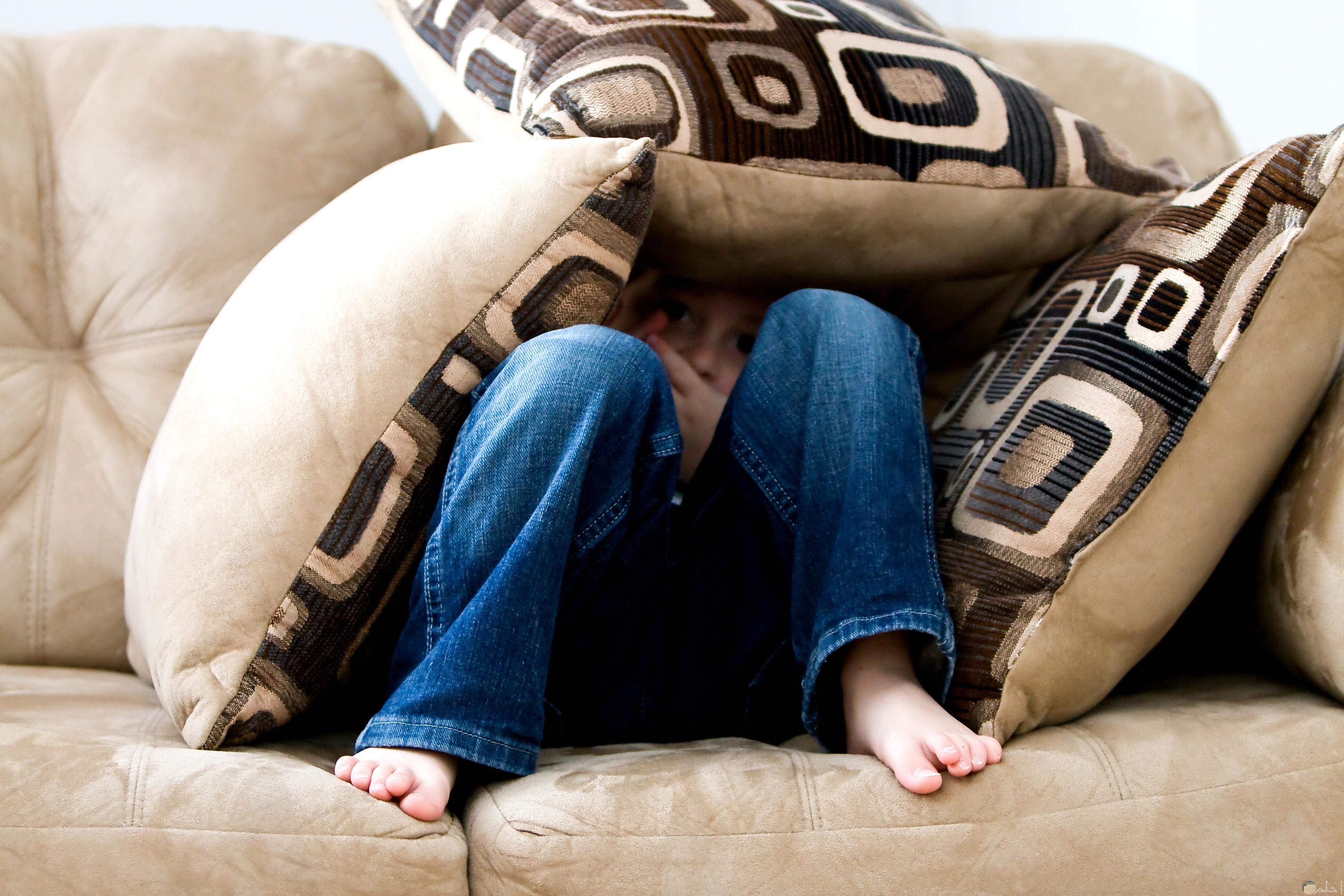 صورة طفلة حزين يختبيء تحت الوسادة