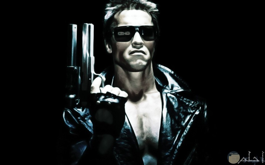 رجل يرتدي جاكت اسود وبيده مسدس ويرتدي نظاره