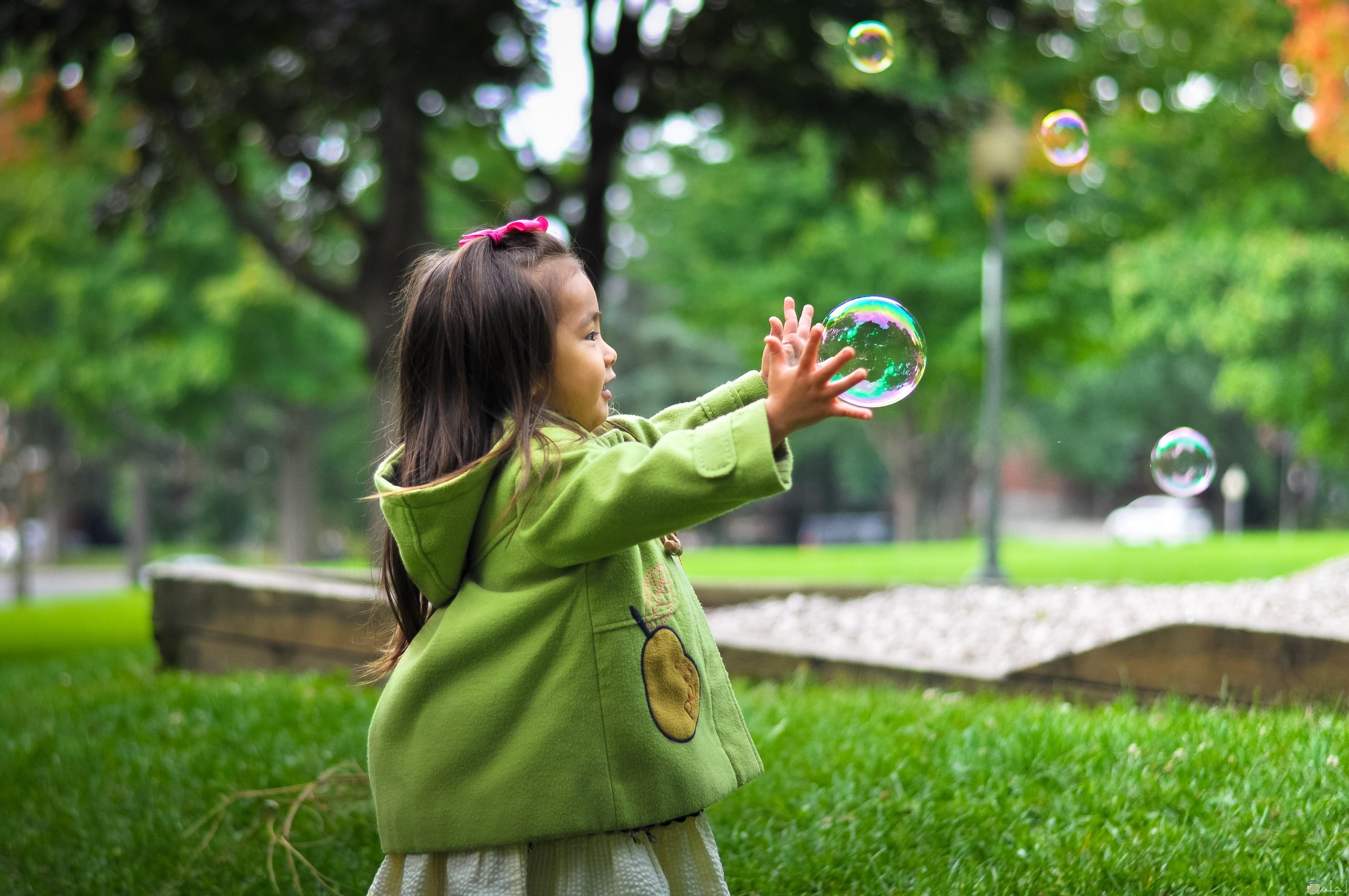 بنت تلعب بالفقاقيع وسط الحديقه